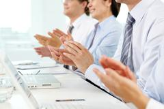 business people sitting in a row applauding cheerfully to their successful colle - stock photo