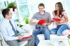 financial agent holding a meeting with a young family at home discussing the ter - stock photo