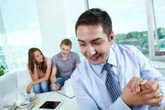 cunning manager rubbing his hands while his unaware clients signing the contract - stock photo