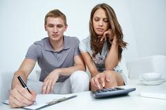 young couple coming across some imbalance planning their family budget - stock photo