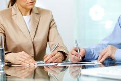 business partners taking notes at seminar or meeting - stock photo
