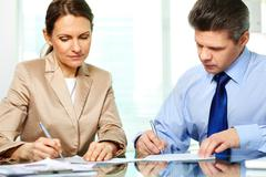 business partners working with papers by the table in office - stock photo