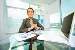 cheerful business lady smiling at camera at her workplace - stock photo