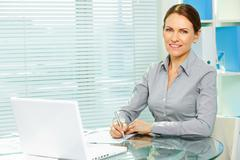 woman successful in business smiling happily at camera - stock photo