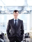 portrait of happy businessman looking at camera with smile - stock photo