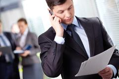 a handsome businessman calling by the phone in working environment - stock photo