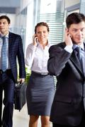 Row of business people speaking on cellular phones Stock Photos