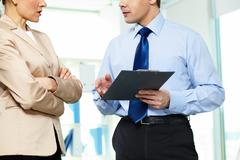 formally dressed business partners discussing papers in office - stock photo