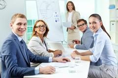 Cheerful team members looking at camera and smiling Stock Photos