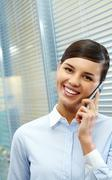 Image of busy businesswoman calling by mobile phone and looking at camera Stock Photos