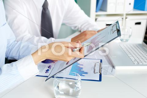 Stock photo of image of human hands during discussion of business documents at meeting