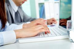 Close-up of businesswoman working with laptop at workplace Stock Photos