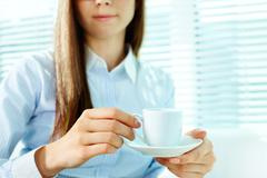 Photo of porcelain coffee cup and saucer in female hands Stock Photos