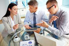 energetic business people discussing the results of the latest strategic movemen - stock photo