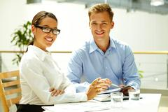 handsome guy and his pretty colleague busy solving some business matters - stock photo