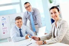 portrait of a modern business team, pretty lady smiling in the foreground - stock photo