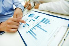close-up of graphs and charts analyzed by business people - stock photo