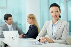 portrait of a young woman at workplace looking at camera and smiling - stock photo