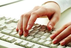 close-up of female hands touching buttons of white computer keyboard - stock photo