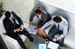 above angle of business group discussing papers - stock photo