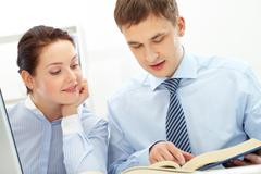 Photo of smart businessman and his pretty colleague reading book in office Stock Photos