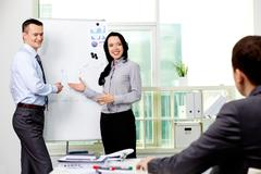 confident business partners carrying out presentation of business plan to manage - stock photo