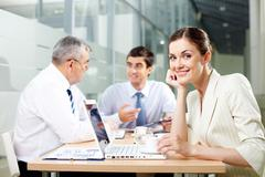 A beautiful businesswoman looking at camera in working environment Stock Photos