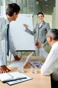 Stock Photo of young businesswoman explaining her ideas on whiteboard at meeting