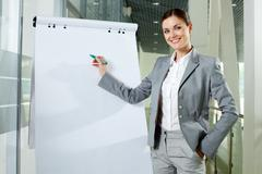 Smiling businesswoman presenting new project on a whiteboard Stock Photos