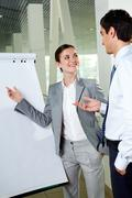 two young associates by whiteboard looking at one another while communicating - stock photo