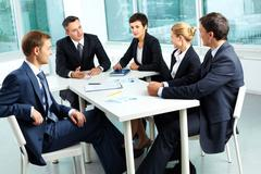 Stock Photo of image of confident colleagues looking at their boss at meeting