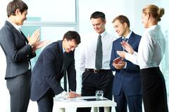 Image of co-workers congratulating their colleague while he signing paper at mee Stock Photos