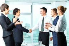 Image of successful co-workers applauding to handshaking men Stock Photos