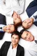 five business people lying in circle, looking at camera and smiling - stock photo