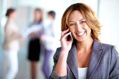 Stock Photo of image of pretty businesswoman calling on the phone in working environment