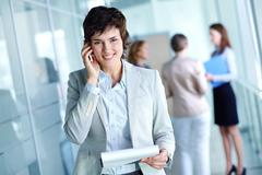 image of busy female calling on the phone and looking at camera in working envir - stock photo