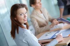 Image of pretty female looking at camera in working environment Stock Photos