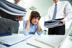 Terrified secretary touching her head while looking at big heaps of papers Stock Photos