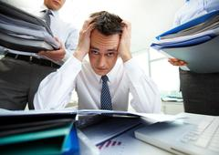 Perplexed accountant touching his head being surrounded by business partners wit Stock Photos