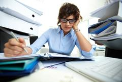 perplexed accountant doing financial reports being surrounded by huge piles of d - stock photo
