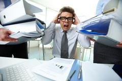 terrified accountant touching his head being surrounded by huge piles of documen - stock photo
