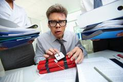 Serious accountant with dynamite being surrounded by big heaps of papers Stock Photos
