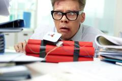 Terrified businessman looking at dynamite Stock Photos
