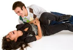 young girl being tickled by young man - stock photo