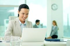 portrait of pretty secretary looking at laptop screen while typing - stock photo