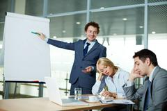 Stock Photo of business people listening to presentation, focus is on pensive female