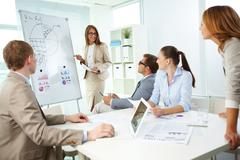 Confident top manager standing by the whiteboard and explaining her strategy at Stock Photos