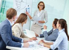 Confident businesswoman explaining something to colleagues at meeting Stock Photos
