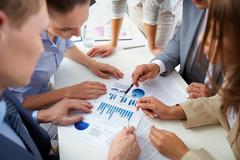 Image of business people discussing business documents at meeting Stock Photos