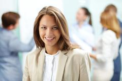 Portrait of pretty business woman looking at camera with working partners on bac Stock Photos